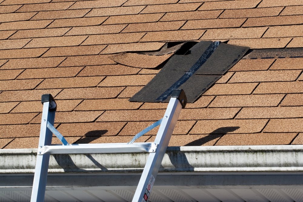 Roof being repaired from wind damage