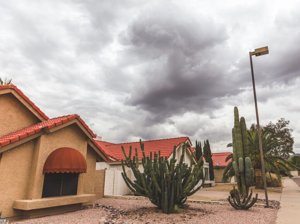 A roof with impending storm clouds. In Arizona, routine roof maintenance can make a world of difference.
