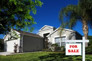 Close up for sale sign in front yard of single family house with palm tree in Florida