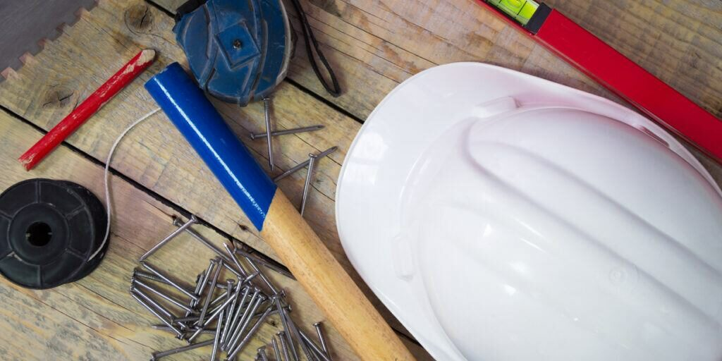 A collection of tools including a hard hat and nails.