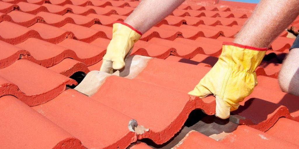 roofer installing red concrete roof tiles
